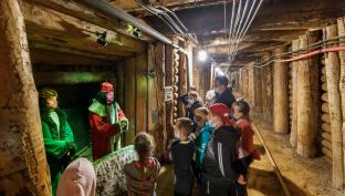 Grupa dzieci w maseczkach stoją w kopalni  i patrzą się na figurki w przebraniach z naklejonymi twarzami.