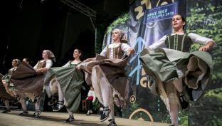 Dziewczyny w regionalnych strojach tańczą na scenie trzymając w rękach boki sukienek