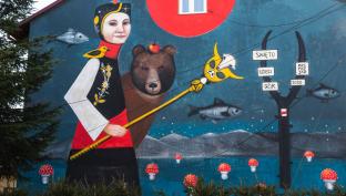 Mural. Kobieta w stroju ludowym, za nią niedźwiedź na ścianie budynku.