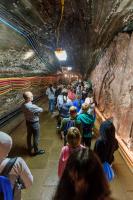 Grupa dzieci tyłem stoi w kopalni.