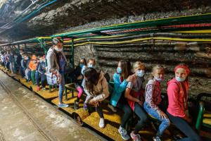Grupa dzieci w maseczkach siedzi na ciufci w kopalni.