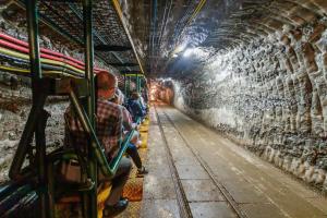 Grupa ludzi siedzi na ciufci w kopalni.