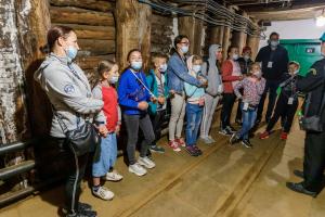 Grupa dzieci z opiekunami w maseczkach stoi w kopalni.