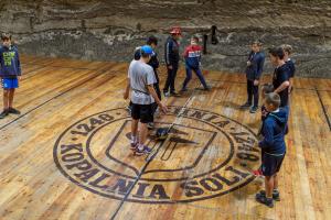 Grupa chłopców stoi na drewnianym boisku. Na środku widać czarną piłkę. Ściany zrobione są z kamienia.