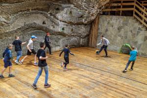 Grupa dzieci gra w piłkę na drewnianym boisku.