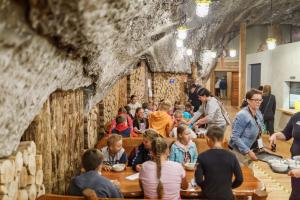 Grupa dzieci z opiekunami siedzą przy drewnianych stołach i jedzą obiad.