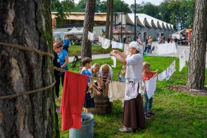 Dzieci wraz z opiekunami bawią się na drewnianych atrakcjach oraz robią kolorowe wiatraczki na drewnianych stołach. Wszystko odbywa się na świeżym powietrzu.