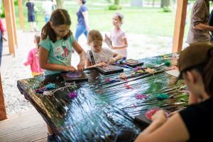 Grupa dzieci wraz z opiekunami siedzą przy stole, wykonując prace plastyczne. Stół znajduje się w środku drewnianej altany.