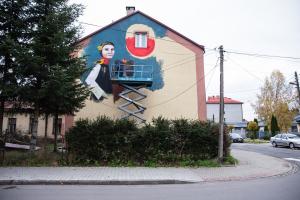 Wykonywanie muralu na ścianie budynku.