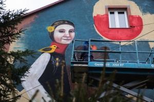 Mural. Kobieta w stroju ludowym na ścianie budynku.