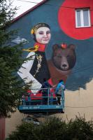 Dwie osoby tworzą mural. Kobieta w stroju ludowym, za nią niedźwiedź na ścianie budynku.