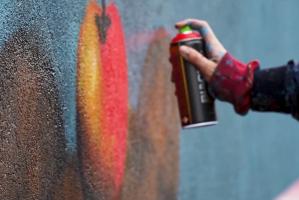 Dłoń trzymającą farbę w aerozolu i malująca po ścianie