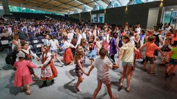 dzieci trzymając się za ręce tańczą w kółeczkach