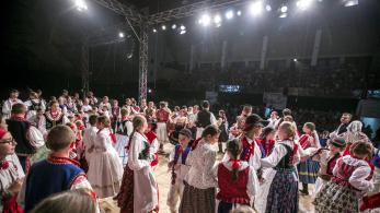 duża liczba dzieci tańczy na scenie, w tle widać publikę, oświetlają ich reflektory