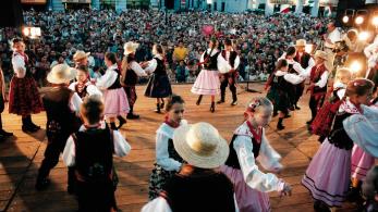 Dzieci w regionalnych stronach tańczą na oświetlonej scenie, za nimi widać liczną publiczność