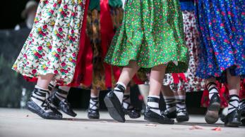Nogi i regionalne spódnice dzieci tańczących na scenie