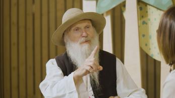 starszy mężczyzna z białą, długą brodą, na głowie ma ludowy kapelusz