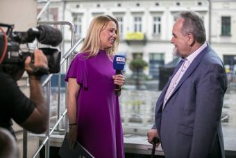 Kobieta przeprowadza wywiad z mężczyzną, w ręku trzyma mikrofon, na pierwszym planie widać filmowca z kamerą