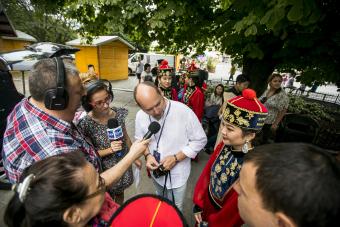 Kilka osób zebranych w kręgu, część z nich trzyma mikrofony i ma na uszach słuchawki, część się przygląda, jeden mężczyzna mówi do mikrofonu