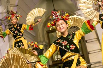 Dziewczynki w zdobionych złotem strojach tańczą z wachlarzami