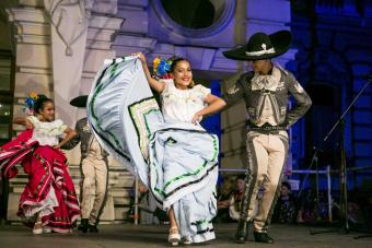 Chłopiec i dziewczynka w meksykańskich strojach regionalnych tańczą na scenie