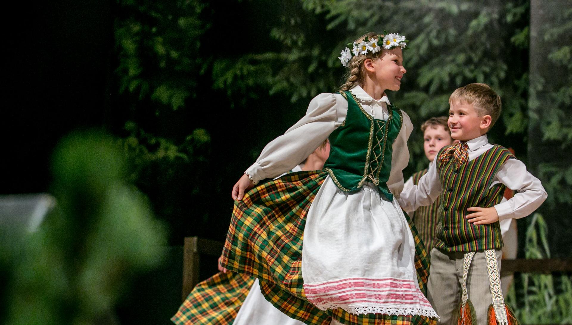 Para dzieci tańczy na scenie. Uśmiechają się. Dziewczynka ma na głowie wianek