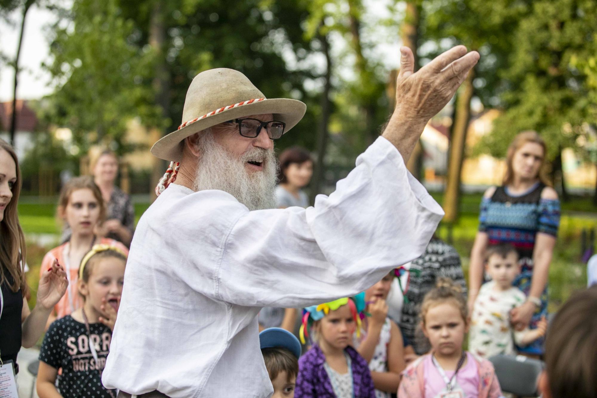 Starszy mężczyzna w lnianym regionalnym stroju stoi wśród dzieci, ma podniesioną rękę