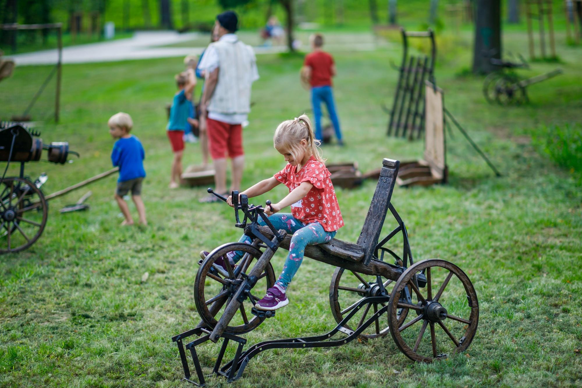 dziewczynka siedzi na starym, trójkołowym, metalowym rowerze